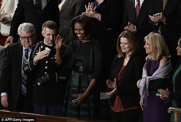 Acknowledgement: US First Lady Michelle Obama (C) stands with US Army Ranger Cory Remsburg (2nd-L), who was wounded in Afghanistan, before President Barack Obama's State of the Union address before a joint session of Congress