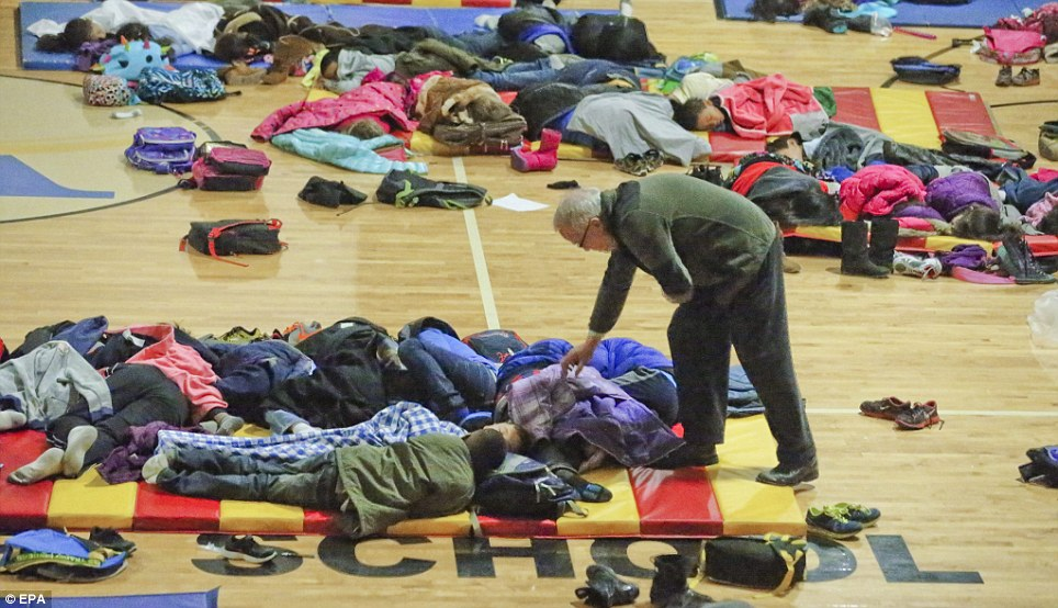 A teacher at E. Rivers Elementary school covers sleeping children in the gymnasium of the school who were forced to stay in the aftermath of a winter storm in Atlanta, Georgia on Tuesday night