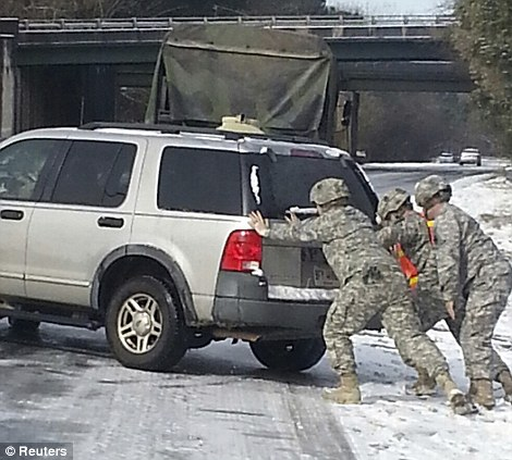 Georgia Army National Guard photo shows Staff Sgt. Andrew Huffman and soldiers of the Georgia National Guard's 48th Infantry Brigade Combat Team, 2nd Battalion 121st Infantry Company assisting stranded motorists following a rare ice storm in Atlanta