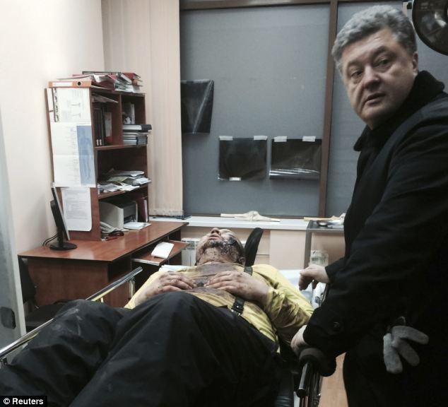 Opposition leader Petro Poroshenko (right) rushed to the hospital where Bulatov (left) was taken