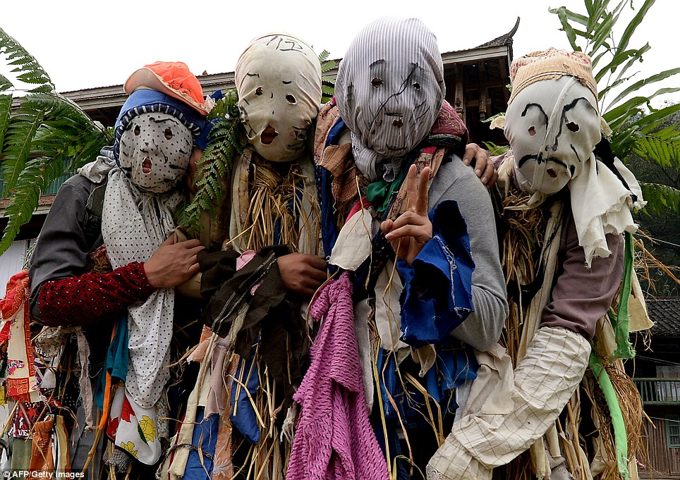 Miao Minority villagers dress as spirits at a traditional horse fighting competition in China's Guangxi Province as part of New Year celebrations