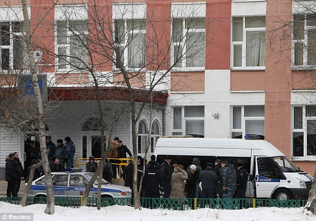 Police gather outside the school north of Moscow where a student went on the rampage with a rifle shooting dead a policeman and teacher