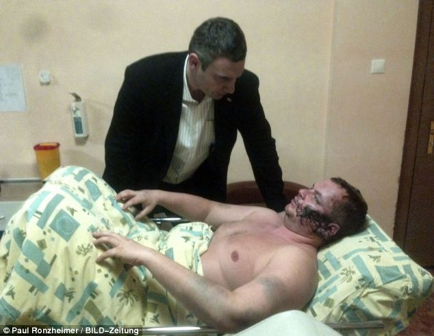 Ukrainian opposition leader Vitali Klitschko speaks to Dmytro Bulatov in the Kiev hospital where he is receiving treatment after the alleged kidnapping