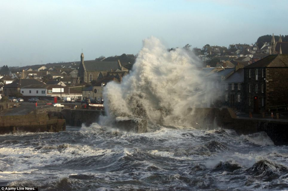 Buildings on the sea front in Porthleven, Cornwall are dwarfed by a huge wall of water crashing on the front