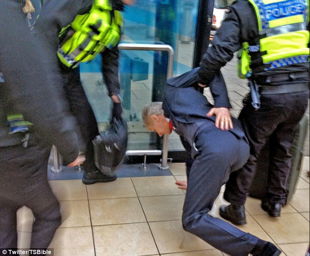 Back on track: Another police officer helps Wenger with his bag as he is brought back up