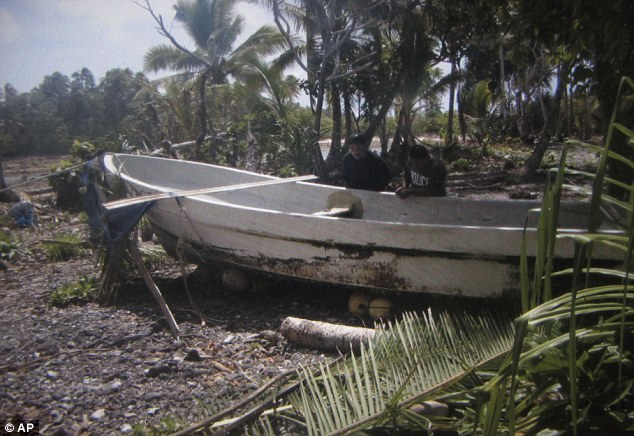 Boat: Willing Kajidrik also released a photo of police checking the 7-meter fishing boat of Jose Salvador Alvarenga after it was pulled onto the shore following his rescue, on Marshall Islands