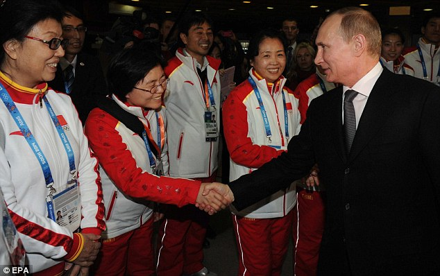 Vladimir Putin (R) shake hands with Chinese athletes during the Winter Olympics in Sochi