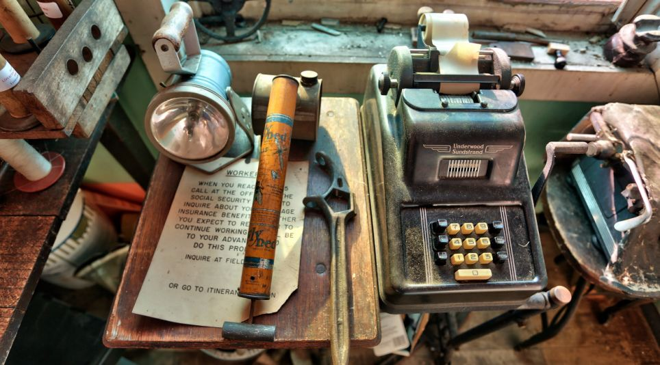 Forgotten: An Underwood Sundstrand adding machine sits alongside an old lamp and a notice advising staff to enquire about the company's insurance benefits