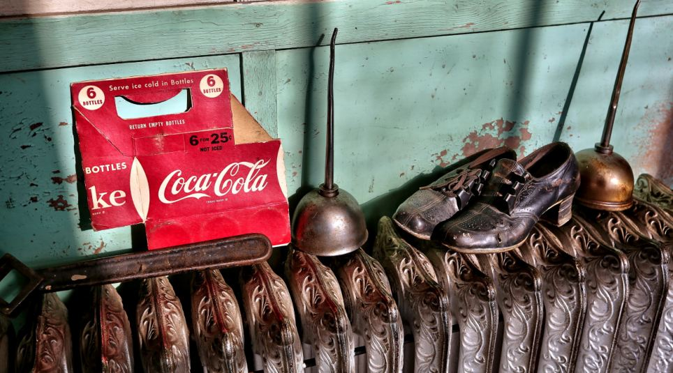 An empty multipack carton for Coca-Cola bottles sits on a radiator alongside two oil cans and a forgotten pair of women's brogues in the Maryland factory