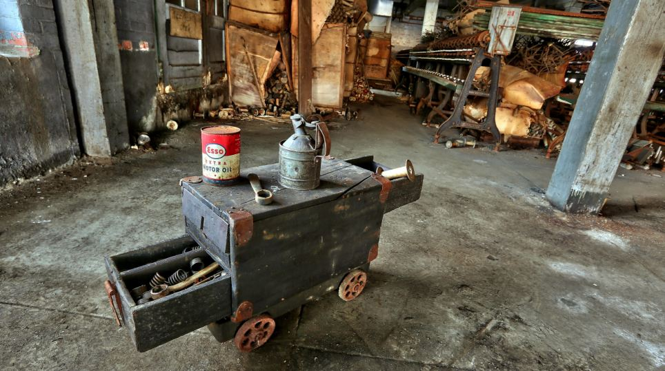 A can of Esso motor oil sits on a homemade portable tool box. The rickety look of many of the items on the site make them seem even older than they actually are
