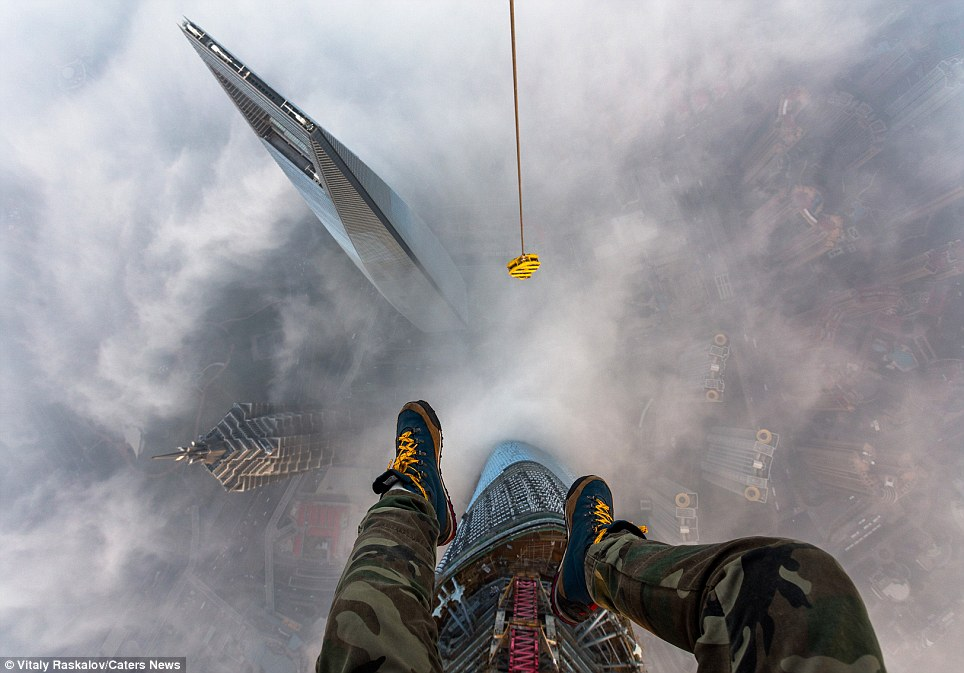 The view from the heavens: Vitaly Raskalov's feet dangling from the top of the Shanghai Tower