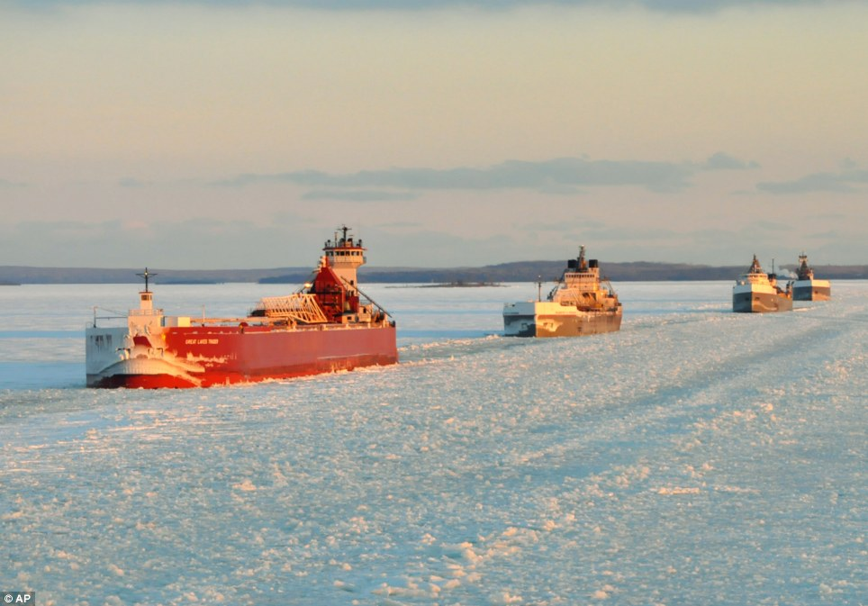Hard work: A convoy of Great Lakes cargo ships line up to follow an icebreaker on the St. Marys River, which links Lakes Superior and Huron, as 88 per cent of the Great Lakes' surface is now reported frozen