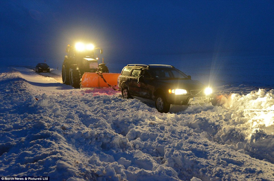 Deep snow: Motorists find themselves stranded in deep snow as blizzards trap their cars along a Pennines road overnight Thursday. A number of cars became stuck during heavy snow and gale force winds on a road between Cumbria and County Durham, England, and had to be rescued by a farmer