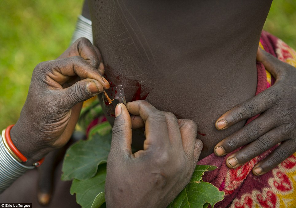 Ceremony: A Surma scarification ritual using thorns and a razor is carried out on a 12-year-old girl who volunteered to be scarred