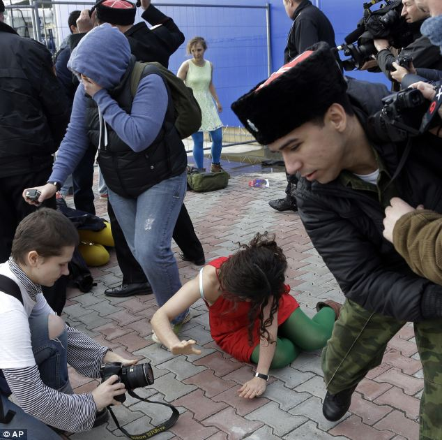 A member of the punk group Pussy Riot lies on the ground. They only been performing for a few seconds when they were set upon by Cossacks