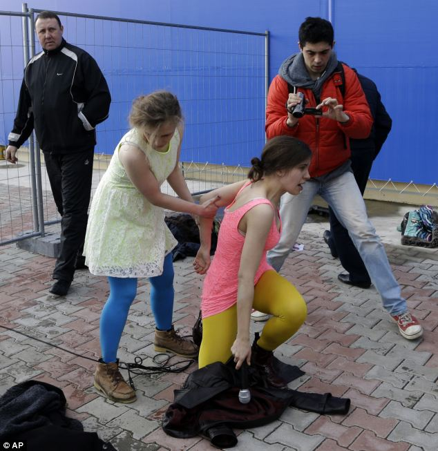 Maria Alekhina, second left, helps Nadezhda Tolokonnikova get up after they and other members of the punk group Pussy Riot are attacked by about a dozen Cossack militiamen