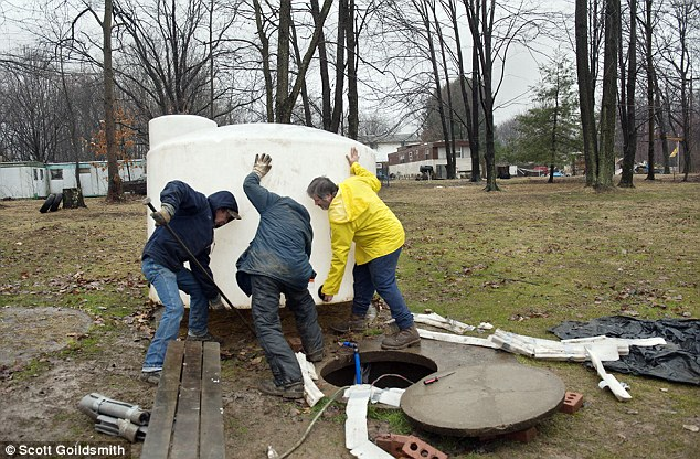 """John """"Denny"""" Fair, 58, was among several residents who lost their water supply when gas driller Rex Energy ended water shipments to several families in Connoquenessing Township, Butler County. Workers hauled away two tanks from his backyard that supplied water to three homes. Fair is in the middle helping workers remove his only supply of potable water - he just wanted to get the removal process over with."""