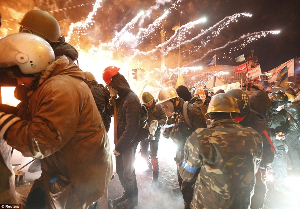 Fireworks explode near anti-government protesters during clashes with riot police at Independence Square in Kiev on February 18