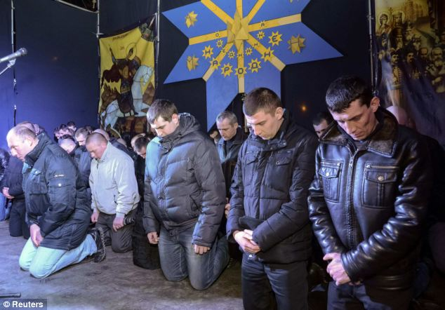 Riot police kneel as they apologize to Lviv residents for taking part in an operation against anti-government protesters in Kiev