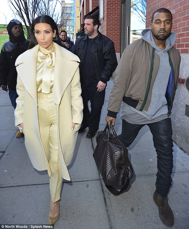 Not even a chuckle: Kanye kept up the petulant stance as he stepped out with a ravishing in cream Kim Kardashian on Monday