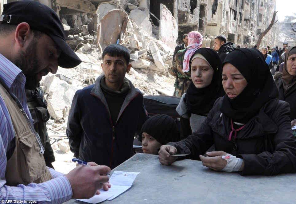 Desperate need: A sick young woman is queuing up for a food parcel and medical assistance alongside her family in Yarmouk