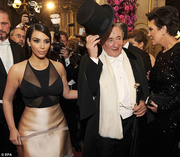 A trooper: Though he had insulted her, the Kardashian Kollection designer still took Lugner's arm as they walked into the event with mom Kris Jenner to her left