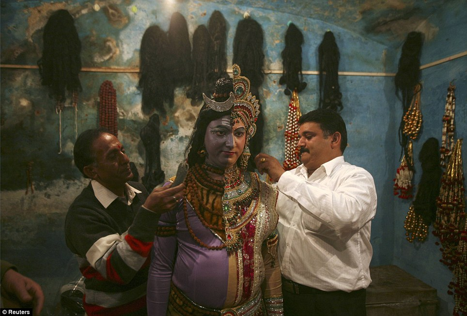 Preparation: A man is helped into his costume which is 50 per cent Lord Shiva and 50 per cent his wife, the goddess Parvati