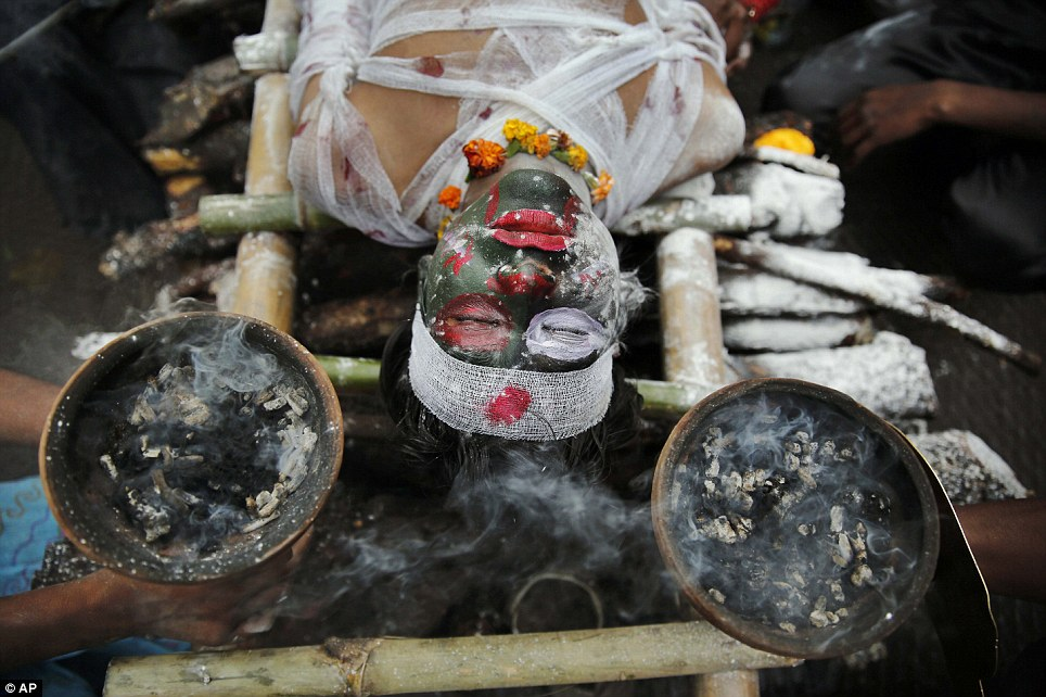 Watch out! A worshipper dressed as a demon lies on a (pretend) funeral pyre during the Shivrati celebrations in the Indian city of Allahbad