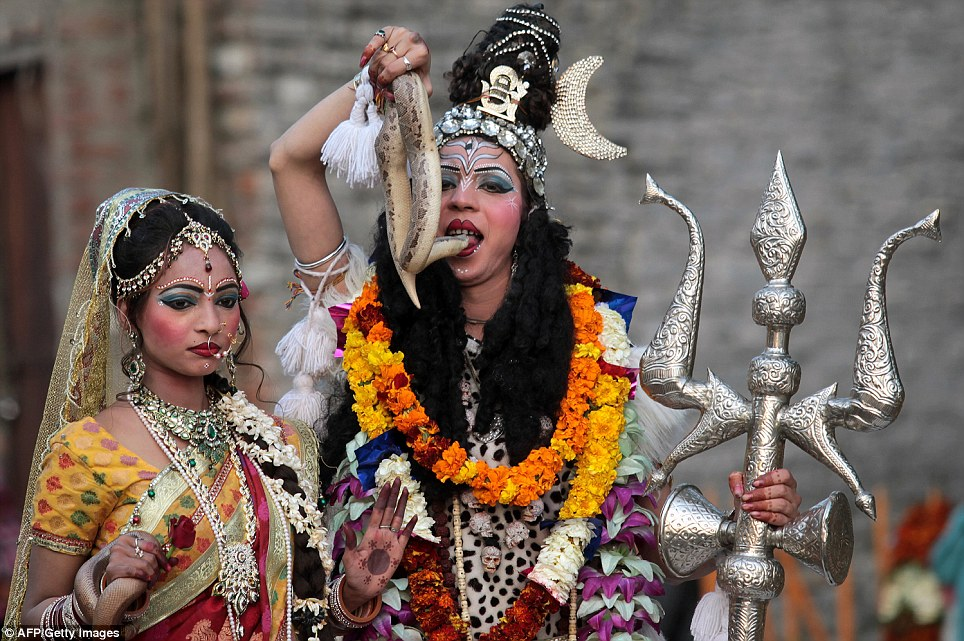 Beautiful: Hindus dressed as Lord Shiva (right) and his wife Mata Pavarti (left) wave to the crowds as they process through the streets of Jammu