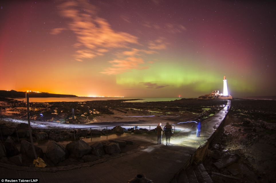Spectacular: People watch the Northern Lights, dance over St. Mary's Lighthouse in Whitely Bay just outside Newcastle