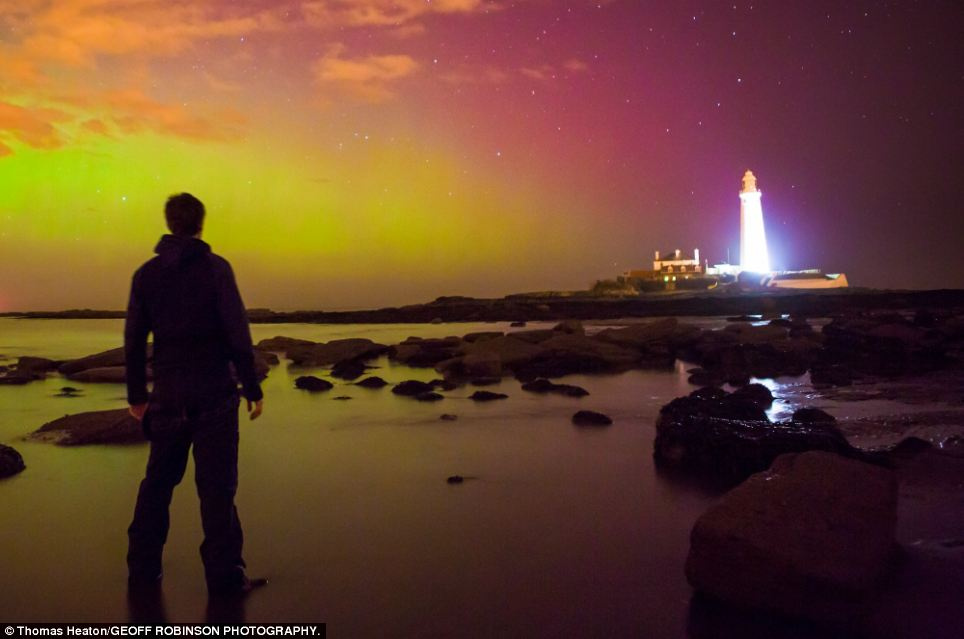 Watching in awe: A man watches the spectacular array of lights, which have caused the lighthouse to gleam a blinding shade of white