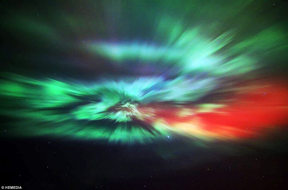 Swirl of colour: Photographer Stewart Watt captures the Aurora Borealis lighting up the sky over the small town of Thurso in Caithness, Scotland, during the night