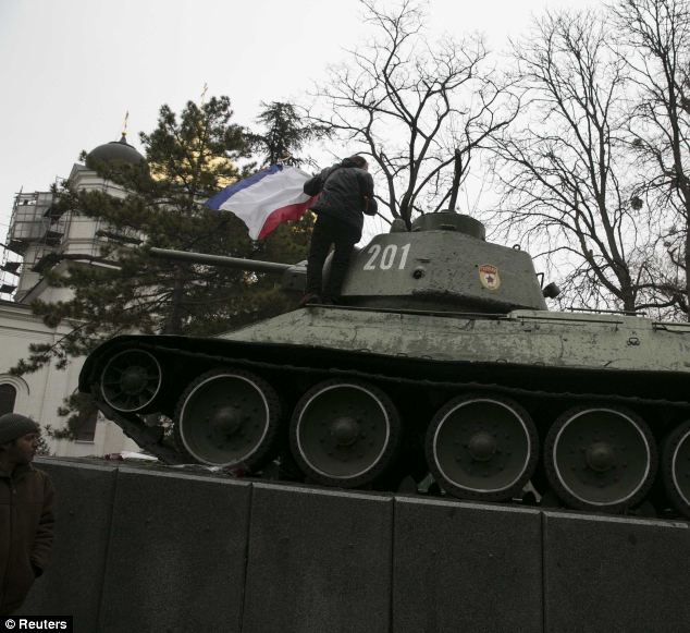 An ethnic Russian Ukrainian man holds the Crimea flag on top of an old Soviet tank during rallies near the Crimean parliament building yesterday