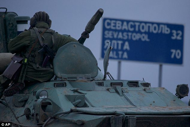 Tensions rising: A Russian soldier on an armoured personnel carrier halted on a road in Ukraine around 20 miles from Sebastapol, where there is a large Russian military presence