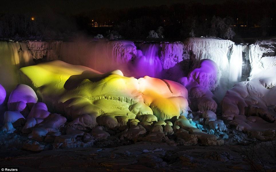 Congelados: Luzes que geralmente refletem a água das Cataratas do Niágara iluminar o gelo depois que ele congelou na segunda-feira