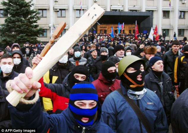Menacing pro-Russian activists take to the streets in Odessa yesterday, many of whom were waving weapons