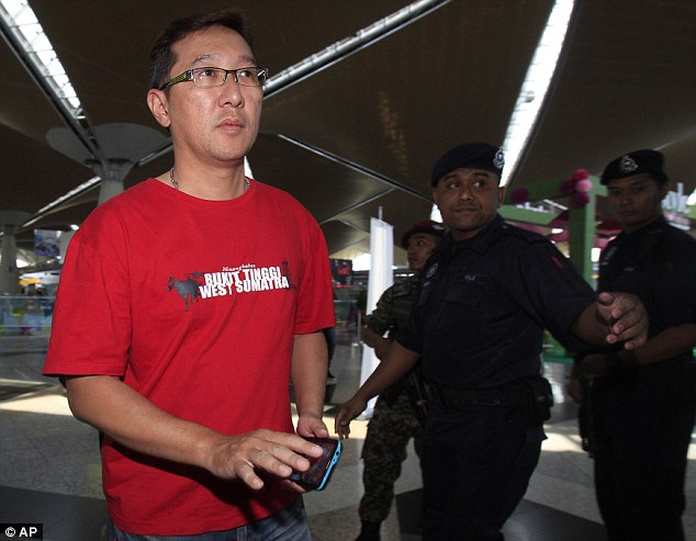 Anxious: A man with family on the missing flight is escorted to the relatives room at Kuala Lumpur airport