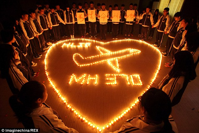 Chinese students stand by candles while praying for the passengers aboard the missing Boeing 777-200 plane of Malaysia Airlines Flight MH370 at a school in Zhuji city, east Chinas Zhejiang province