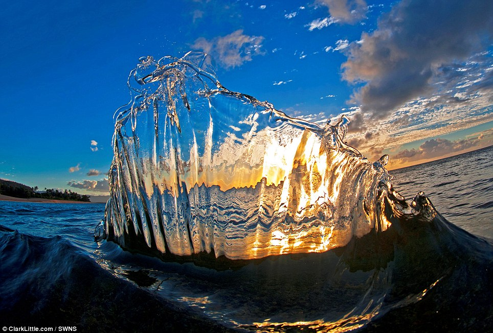 This is the breathtaking moment two waves collide and send a fan of water upwards in front of the setting sun to create a stunning image