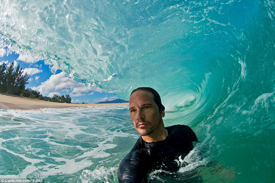 Surf Photographer Mr Little, 44, pictured here inside a tube wave as it breaks on North Shore, Oahu, Hawaii. His tool is a Nikon D300 with a fish eye lens, cased in a waterproof box. The ultra-wide angle fish eye creates a wide panoramic picture