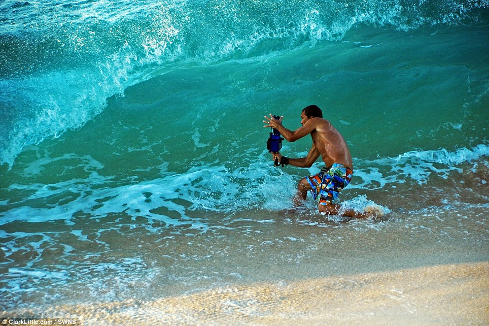 The surf photographer is pictured here lining up his perfect shot moments before the wave is about to crash onto him