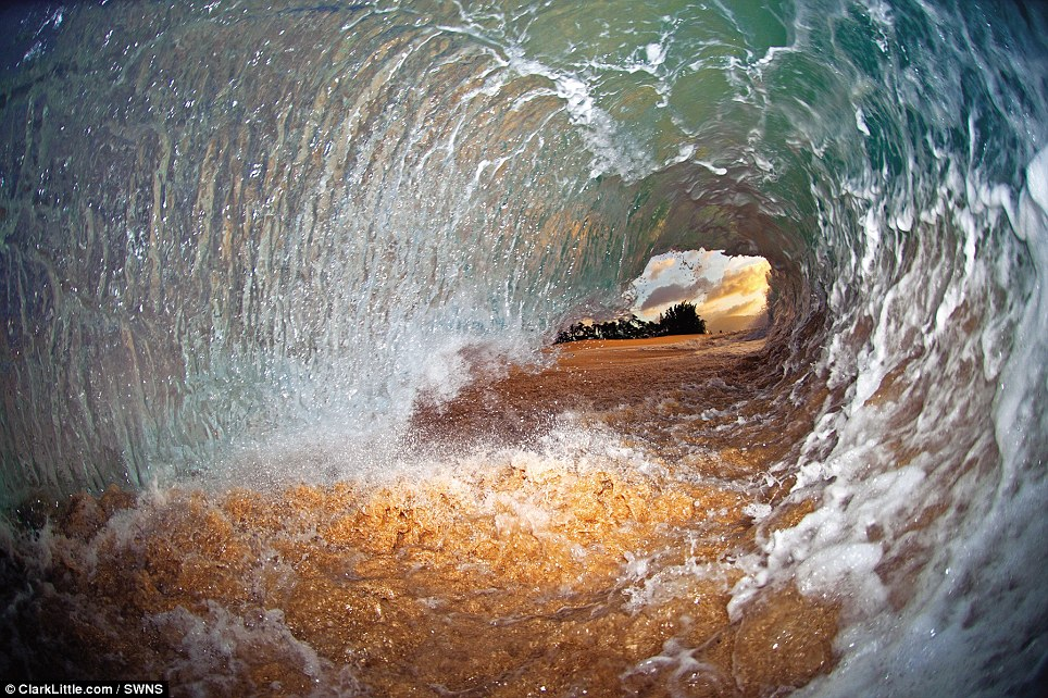 Holding a waterproof camera with an attached strobe flash, the photographer throws himself down on the sand as the wave pitches over and creates an opening with a sunset view in the distance