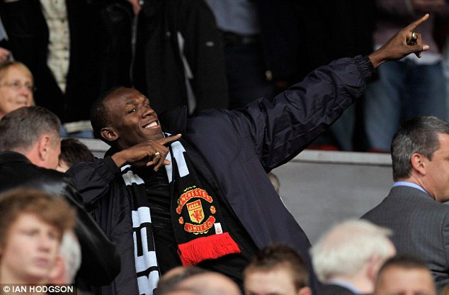 Colourful character: Bolt wears a Manchester United scarf in the crowd at a game against Arsenal at Old Trafford