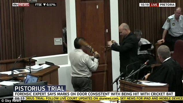 Evidence: Colonel Vermeulen swings the cricket bat which he says was used by Pistorius to break down the toilet door after the Paralympian shot Miss Steenkamp
