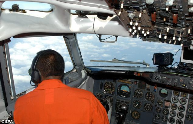 An Indonesian Airforce pilot during a search mission for a Malaysian Airlines aircraft on board a military surveillance plane over the Malacca Straits