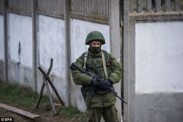 An armed man in military uniform is seen outside the compound of an Ukrainian military base in the village of Perevalnoye, outside Simferopol, Crimea