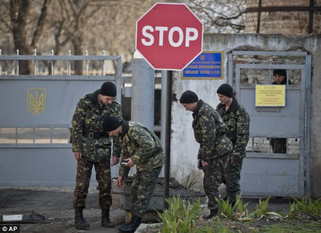 Ukrainian soldiers carry garbage outside the Ukrainian infantry base in Perevalne