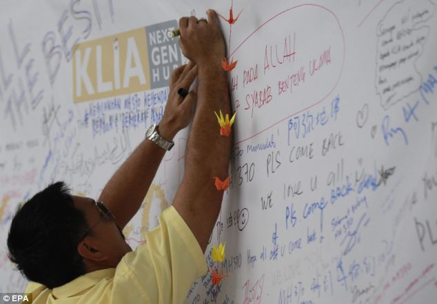 A man writes a message for the passengers of the missing Malaysian Airline plane, on a banner at Kuala Lumpur International Airport