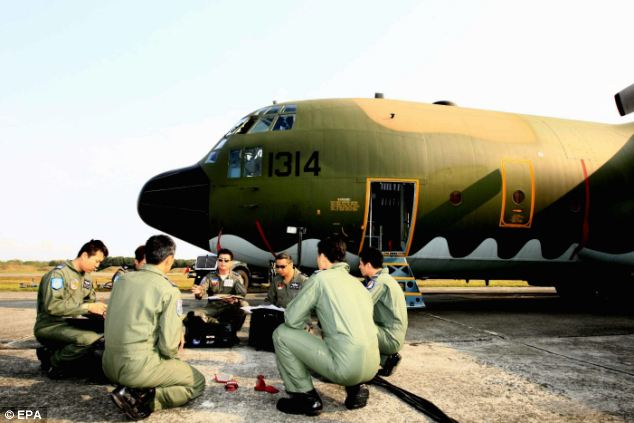 Soldiers discuss the search plan at the Pingtung Air Base in Pingtung County, southern Taiwan, before taking off in a P-130 military transport plane to search for the missing Malaysia Airlines plane over the South China Sea
