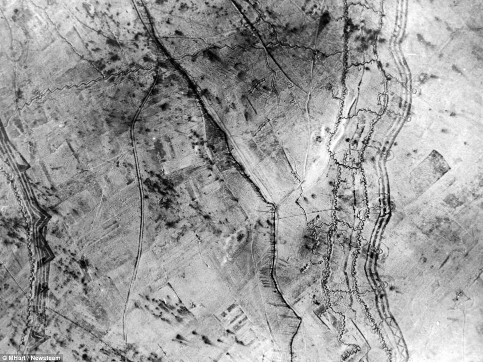 Aerial view: the location and timing of this view is unknown but it shows something of the scale of trench systems which were used by both the Allies and the Germans. There is very little evidence of shell damage, suggesting that these are newly entrenched areas - which could either by the start of the war, or more likely towards the very end when movement had resumed. They could also be training trenches, although their scale makes that unlikely. On the left of the picture, the trenches have a regular pattern but angular sections jutting out. This was intended to allow for sniper fire to protect against an incursion from no man's land. Across the top of the picture is a lengthy communications trench, which zig-zags to make sniper fire more difficult, and also to make it more difficult for artillery fire to rake it. It connects to other what are more likely to be front line trenches, which are in two rows running from top to bottom of the picture. The trenches are dug in a pattern lik